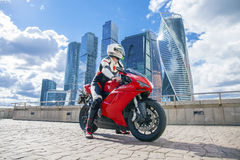 Young man sits on a sports bike on the background of the city sk Royalty Free Stock Photo