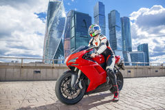 Young man sits on a sports bike on the background of the city sk Royalty Free Stock Images