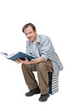 Young man sits on stack of books, holds book and looks to camera Royalty Free Stock Photography