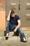 A young man sits on the stairs near the house Stock Image