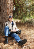 Young the man sits under a tree with a map Stock Image