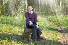 The young man sits in the wood on a stub Royalty Free Stock Image