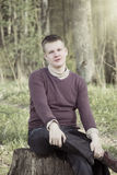 The young man sits in the wood on a stub, retro effect Royalty Free Stock Photos