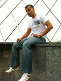 Young man sitting. And looking suspiciously at the camera Stock Photo