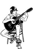 Young man sitting on the acoustic guitar plays music Royalty Free Stock Photo