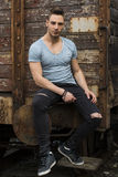 Young man sitting against old rusty train. Looking at camera stock photos