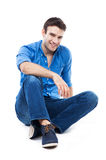Young man sitting against white background Royalty Free Stock Photo