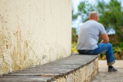 Young man sitting alone on park bench royalty free stock photography
