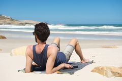 Young man sitting alone at an secluded beach Royalty Free Stock Image