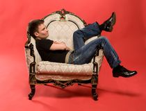 Young man sitting in armchair. Young man sitting in antique armchair, studio portrait, red background Royalty Free Stock Photos