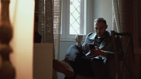 Young man sitting in armchair in living room and using smartphone. Attractive male browse the Internet, drinks coffee. stock video footage