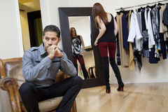 Young man sitting on armchair looking away while girlfriend looking herself in mirror Royalty Free Stock Photos