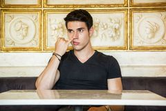 Young Man Sitting At Table Picking Nose Stock Photography