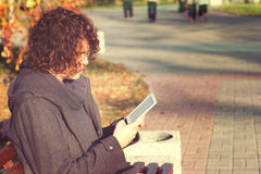 Young man sitting in autumn park and read the electronic book. Stock Images