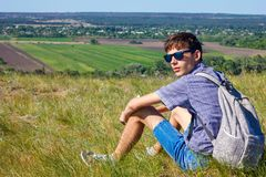 Young man sitting with backpack and looking at beautiful view, tourism concept stock image