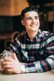 Young man sitting at pub table with a pint of light beer. Young man sitting at bar counter with a pint of light beer stock photography