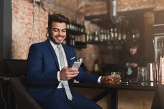 Young man sitting at bar counter and using smartphone royalty free stock image