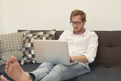 Young man sitting barefoot on couch with laptop Royalty Free Stock Photo