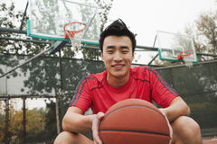 Young man sitting with a basketball on the basketball court, portrait Royalty Free Stock Images