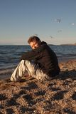 Young man sitting on the beach. Man sits on the shore of Olkhon Stock Photos