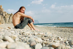 Young man sitting on the beach. Young attrative man sitting on the stones on the beach stock photography