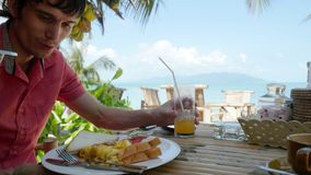 Young handsome man sitting in a beach cafe and eats omelette, toasts, drinks orange juice. Young man sitting in a beach cafe and eats omelette, toasts, drinks Royalty Free Stock Photo