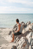 Young man sitting on the beach and look on the horizon line Royalty Free Stock Photo