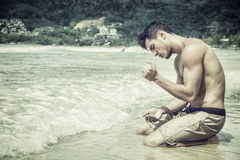Young man sitting on beach playing with sand Royalty Free Stock Images
