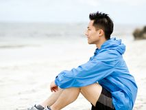 Young man sitting at the beach in sportswear. Young man in sportswear sitting at the beach Stock Photo