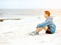 Young man sitting at the beach in sportswear Royalty Free Stock Images
