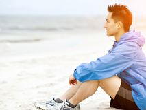 Young man sitting at the beach in sportswear. Young man in sportswear sitting at the beach Royalty Free Stock Photo