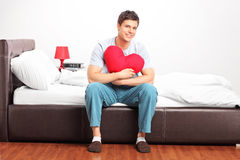 Young man sitting on a bed Royalty Free Stock Photography