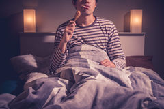 Young man is sitting in bed and eating chicken Royalty Free Stock Photo