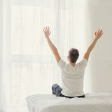 Young man sitting on bed with hands raised up Stock Photo
