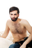 Young man sitting on the bed. Stock Photos