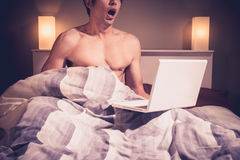 Young man is sitting in bed and watching pornography on laptop Stock Image