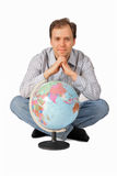 Young man sitting in behind the globe. Isolated on white background Stock Images