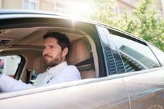 Young man driving his car through city streets royalty free stock photography