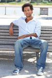 Young man sitting on bench Royalty Free Stock Images