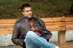 Young man sitting on a bench in autumn park Stock Photography