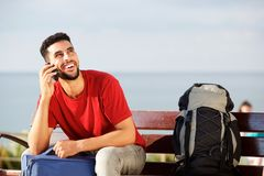 Young man sitting on bench with bags and talking on mobile phone. Portrait of young man sitting on bench with bags and talking on mobile phone Stock Photo