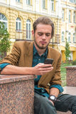 A young man sitting on a bench with cell phone Stock Images