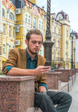 A young man sitting on a bench with cell phone Stock Photos