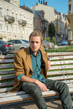 A young man sitting on a bench Royalty Free Stock Photo
