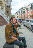 A young man sitting on a bench Stock Photography