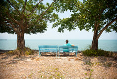 Young man sitting on bench facing the sea Stock Photo