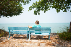 Young man sitting on bench facing the sea Stock Images