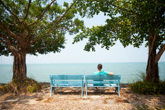 Young man sitting on bench facing the sea Stock Photography