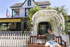 Young man sitting on a bench in front of a American  Style House. American  Style House with  garden ,white  fence and wooden bench  in the front Royalty Free Stock Images