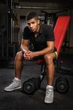 Young man sitting on bench at gym Stock Images